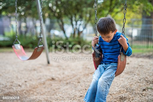 A serious six or seven year old boy swings by himself on a playground