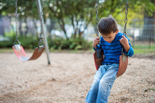 Young boy swinging by himself on playground stock photo
