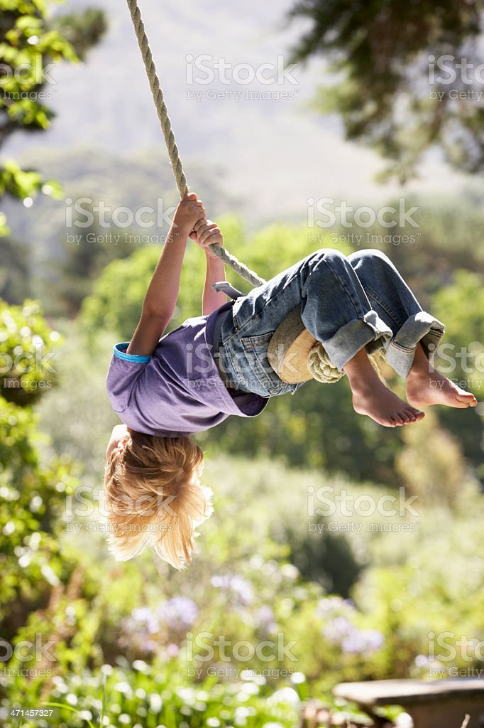 Young boy swinging on a rope tied from a tree stock photo