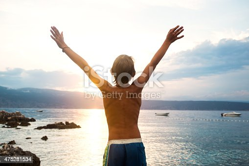 973962328 istock photo young boy  taking a deep breath at the sunset 475281534