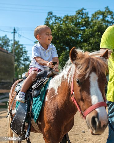Boy enjoying pony ride, father watching him