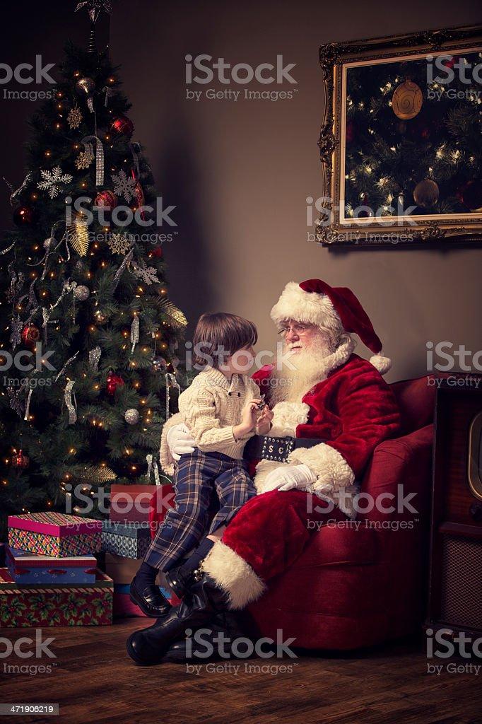 Young boy telling Real Santa Claus his Wish royalty-free stock photo
