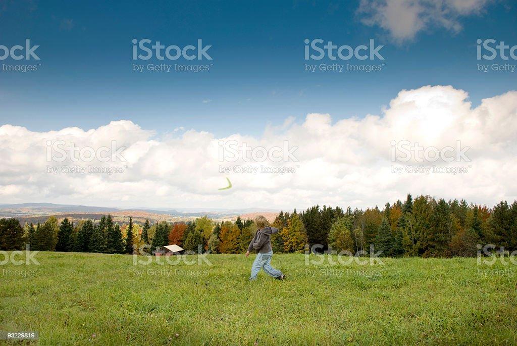 Jeune garçon lancer boomerang les montagnes en arrière-plan l'automne - Photo