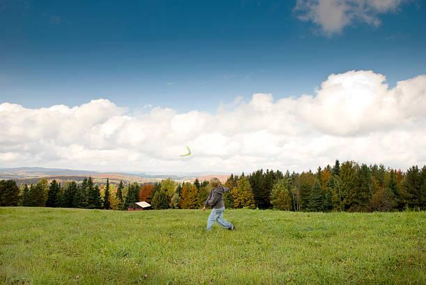 Giovane ragazzo lanciare boomerang montagna sullo sfondo autunno - foto stock