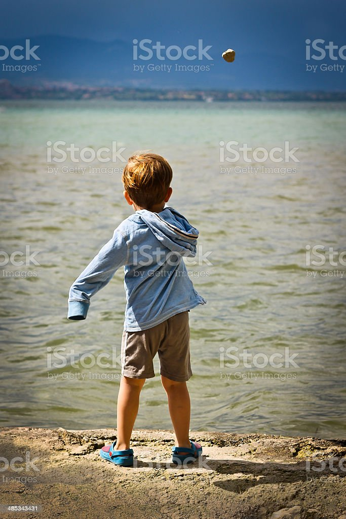 Young boy throwing stone into lake stock photo