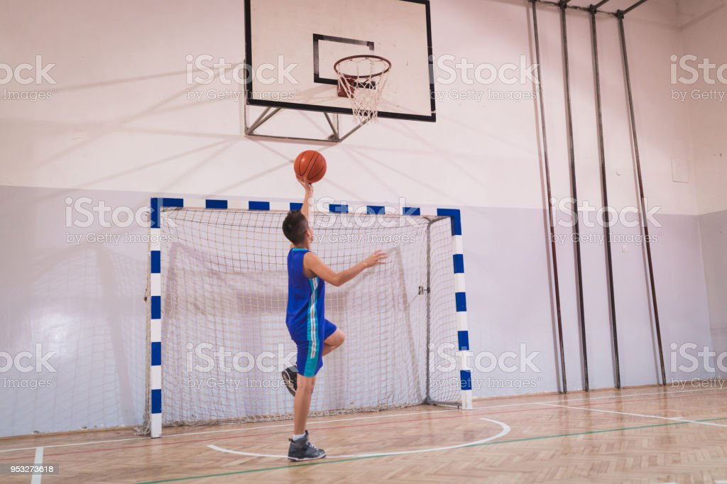Young boy training for a basketball game indoors