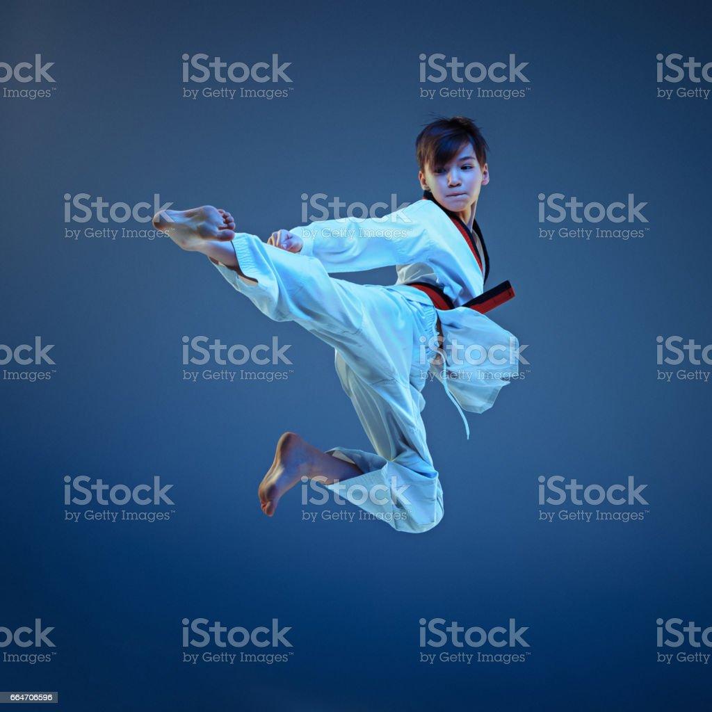 Young boy training karate on blue background stock photo