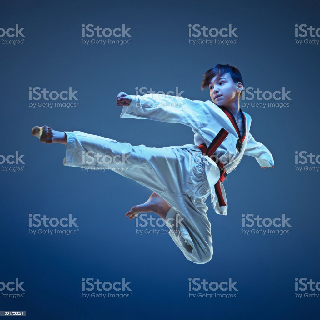 Young boy training karate on blue background stock photo