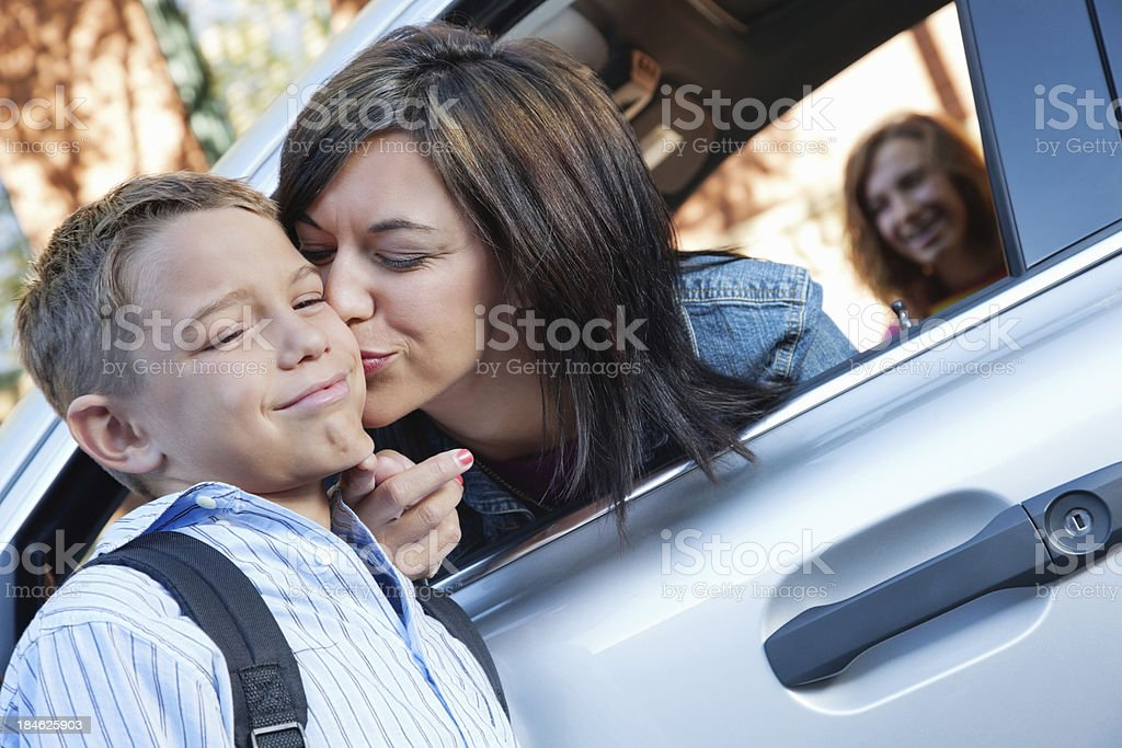 Young boy upset with mom's goodbye kiss at school stock photo