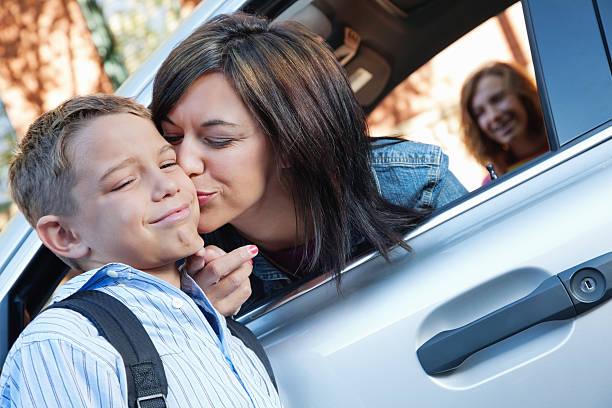 giovane ragazzo arrabbiato con la mamma addio bacio a scuola - kids kiss embarrassed foto e immagini stock