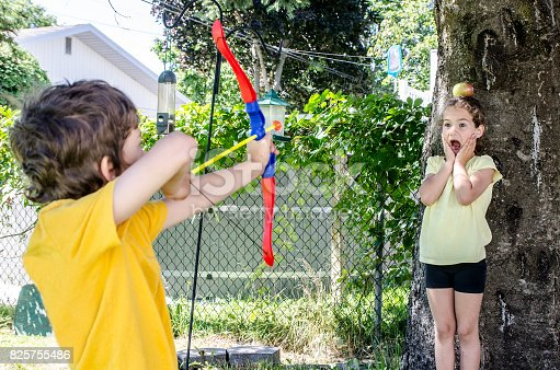 istock Young boy using a bow and arrow and aiming at apple on the head of his sister during a summer day 825755486