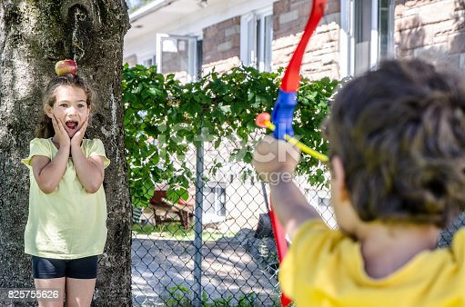 istock Young boy using a bow and arrow and aiming at apple on the head of his sister during a summer day 825755626