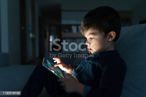 Portrait of a young boy using an app on a digital tablet at home at nighttime – lifestyle