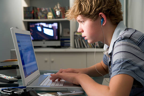 Young boy using a laptop and listening to MP3 player at home stock photo