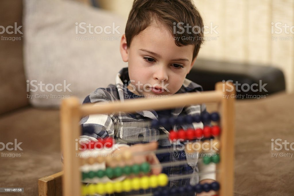 A young boy using an abacus with a blurry background foto