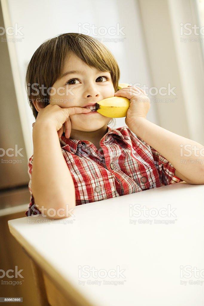 Young boy using banana as phone royalty-free stock photo