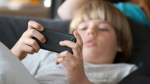 young boy using mobile phone - mobile game stock photos and pictures