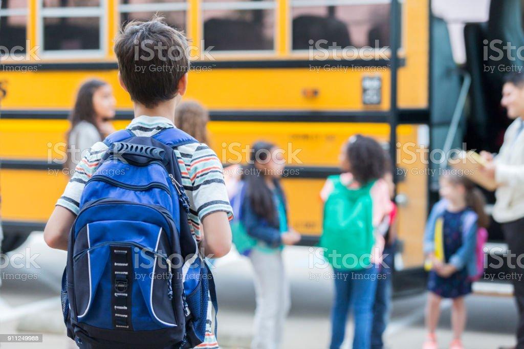 少年がスクールバスをロードするまで待機します。 ストックフォト