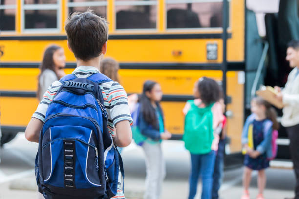 Young boy waits to load school bus stock photo a218f95e05b18