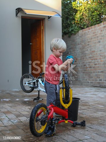 A young boy washes his bike in his back yard of his home.