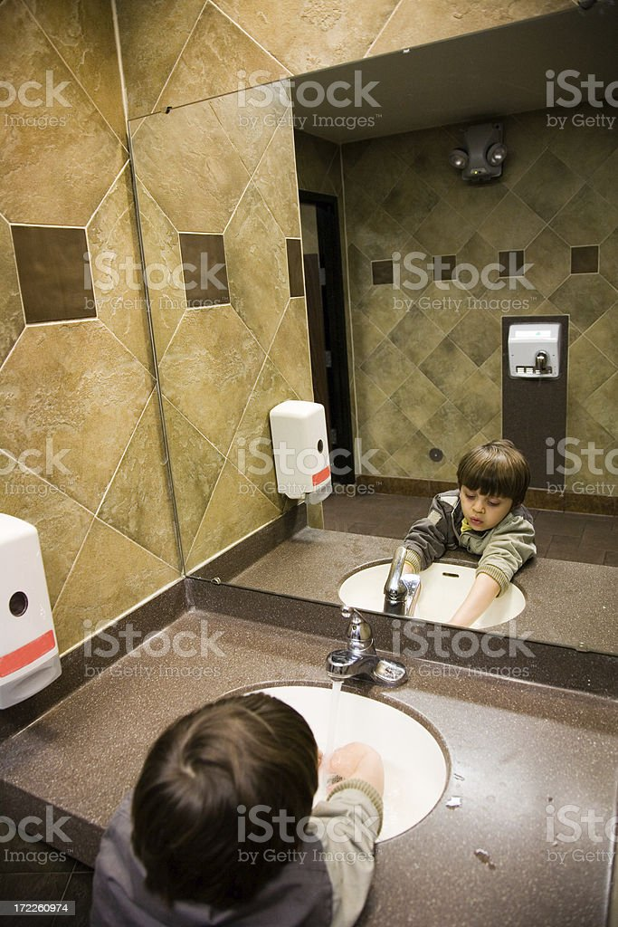 Young boy washing hands in public restroom royalty-free stock photo