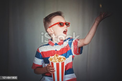 Young boy watch a movie in 3D glasses at the cinema or at home. Little kid eat popcorn over gray background. Home theater. Cute Child in vintage cinema eyeglasses. Entertainment concept.