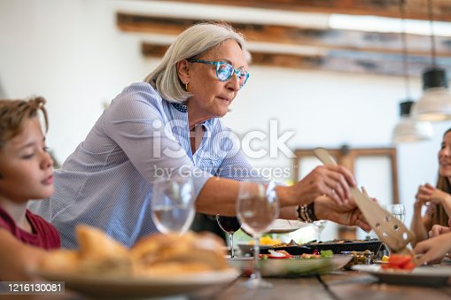Low angle close-up of 11 year old Spanish boy watching his 69 year old grandmother toss salad before serving at traditional midday meal.