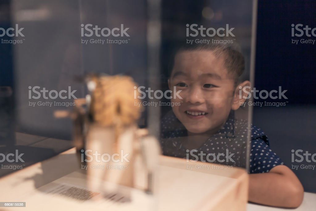 Young boy watching crafts indoors stock photo
