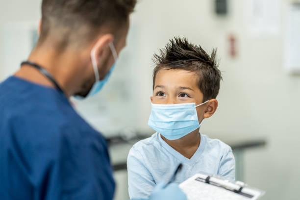 jeune garçon utilisant un masque à un rendez-vous de médecins - masque enfant photos et images de collection