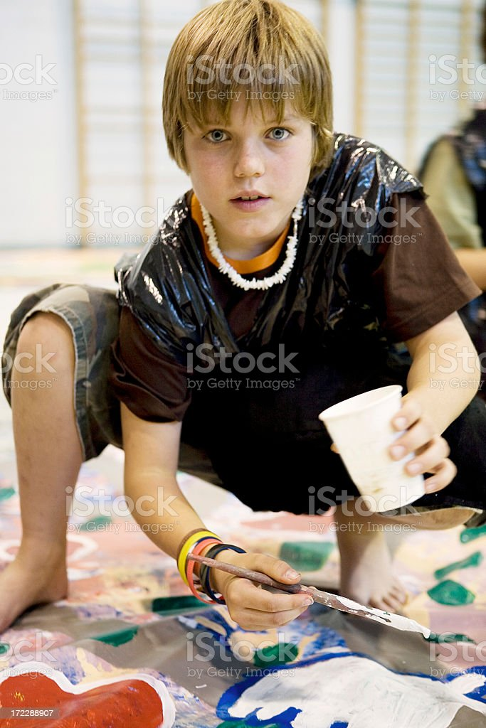 Young boy wearing a trash bag smock and painting a banner royalty-free stock photo