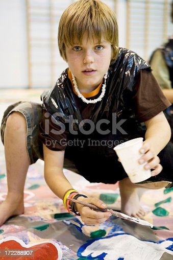 istock Young boy wearing a trash bag smock and painting a banner 172288907