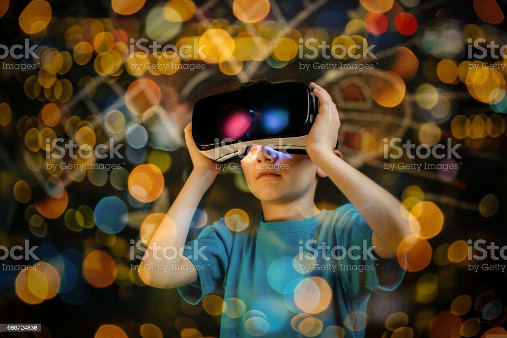 Jovem rapaz vestindo e aprendizagem com um VR óculos. - foto de acervo