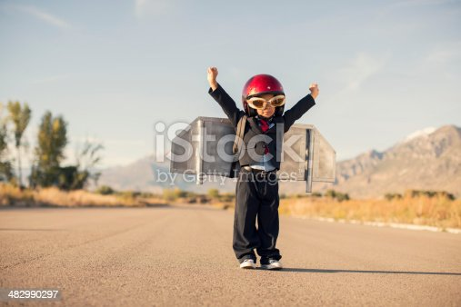 istock Young Boy Wearing Business Suit and Jet Pack Flies 482990297