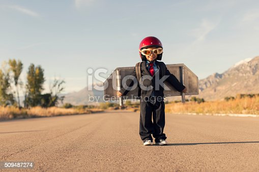 472091427 istock photo Young Boy Wearing Business Suit and Jet Pack Flies 509487274