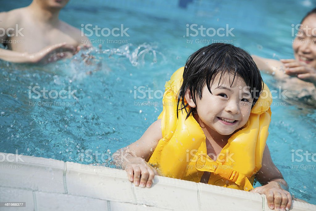 Young boy wearing flotation device holds onto edge of pool stock photo