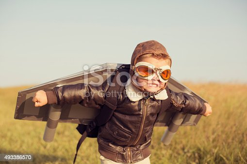 A young boy wearing a bomber jacket and goggles is ready to fly his homemade jetpack. He is standing in the tall grass with arms raised on a hill in England ready for adventure.