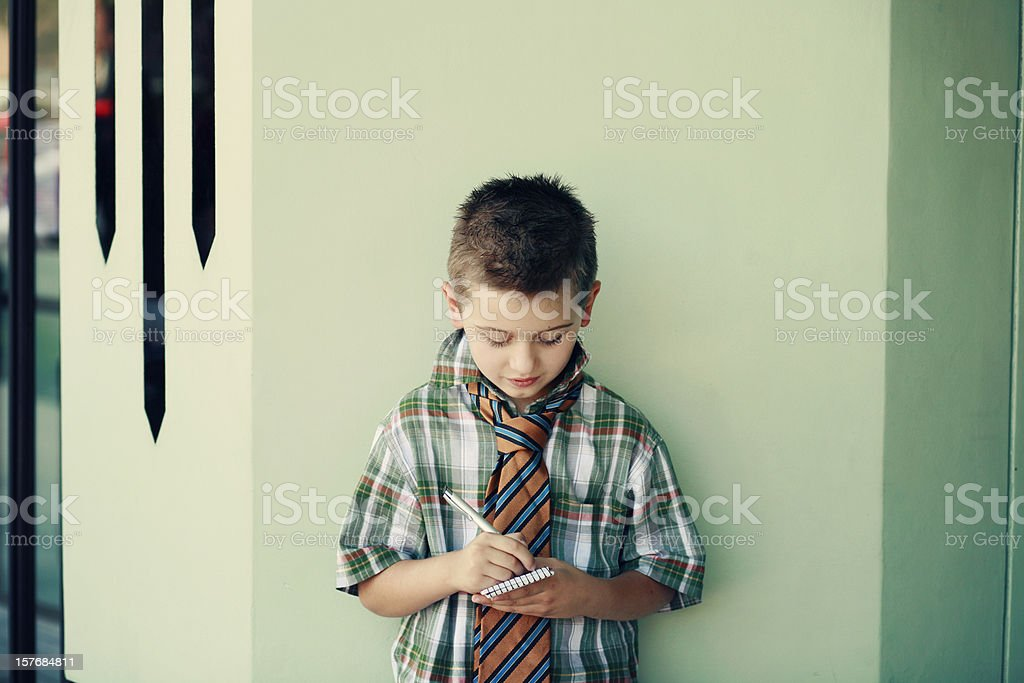 Young Boy Wearing Necktie With Notepad And Pen Stock Photo