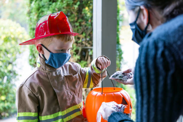 Young Boy wearing protective mask receiving candies on Halloween Young Boy wearing firefighter costume receiving candies on Halloween. A young woman is giving candies at the front door and they are both wearing protective mask. halloween covid stock pictures, royalty-free photos & images