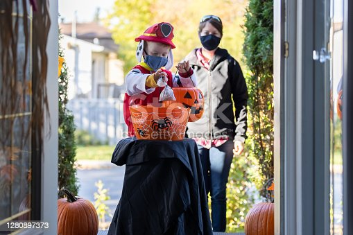Young Boy wearing protective mask taking candies in a self service candy basket on Halloween at front door of a house during COVID-19 pandemic. People are putting a candy basket outside to keep social distancing and let children celebrate Halloween and trick or treat. The little redhead boy is accompanied by his mom.