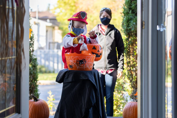Young Boy wearing protective mask taking candies on Halloween at front door of a house Young Boy wearing protective mask taking candies in a self service candy basket on Halloween at front door of a house during COVID-19 pandemic. People are putting a candy basket outside to keep social distancing and let children celebrate Halloween and trick or treat. The little redhead boy is accompanied by his mom. halloween covid stock pictures, royalty-free photos & images
