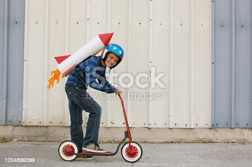 472091427 istock photo Young Boy Wearing Rocket on Scooter 1204896399