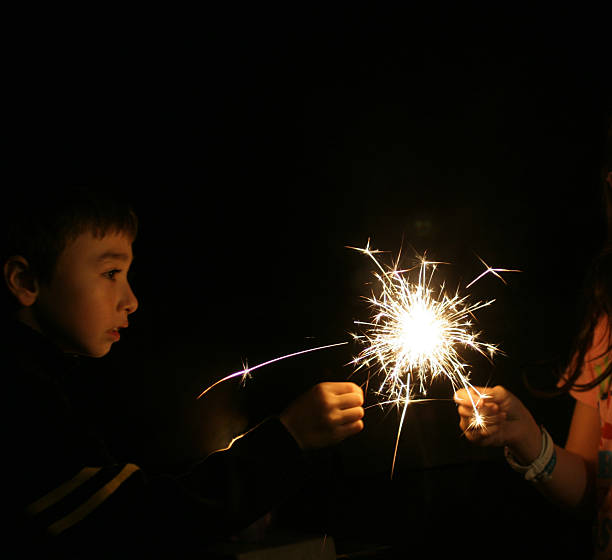 A young boy with a sparkler at night stock photo