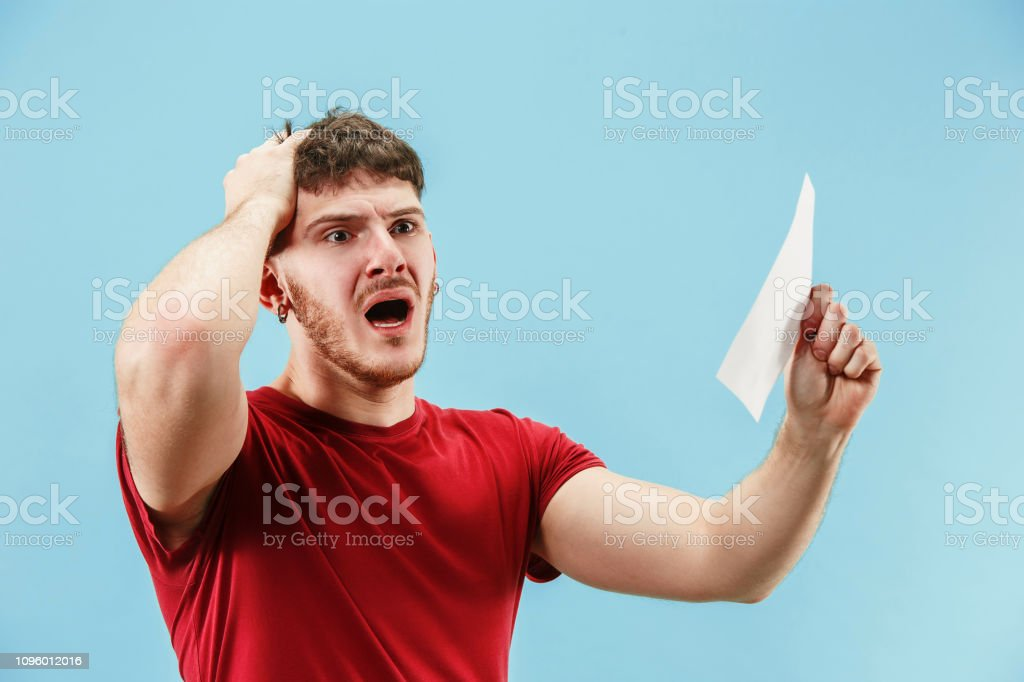 Young boy with a surprised expression bet slip on blue background stock photo