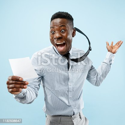 istock Young boy with a surprised expression won a bet on blue background 1132538547