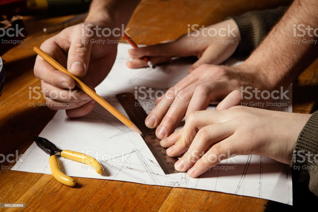 Young boy with a teacher draws a plan of the ship stock photo