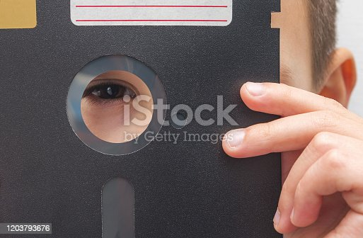Young boy with a vintage 5.25 inch floppy disk. Computer education of children, concept.