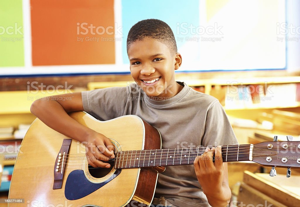 Young boy with acoustic guitar in classroom stock photo