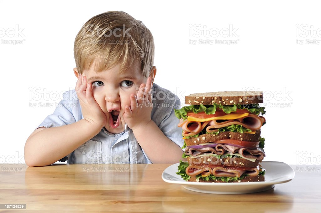 Young boy with an overwhelmed face looking at huge sandwich royalty-free stock photo