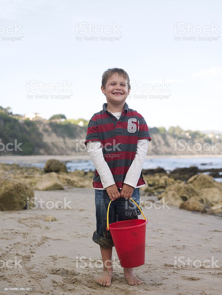 Young boy (6-7) with bucket at beach, smiling royalty-free stock photo