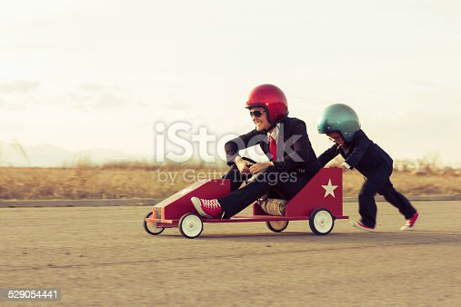 istock Young Boy with Businesswoman Racing a Toy Car 529054441
